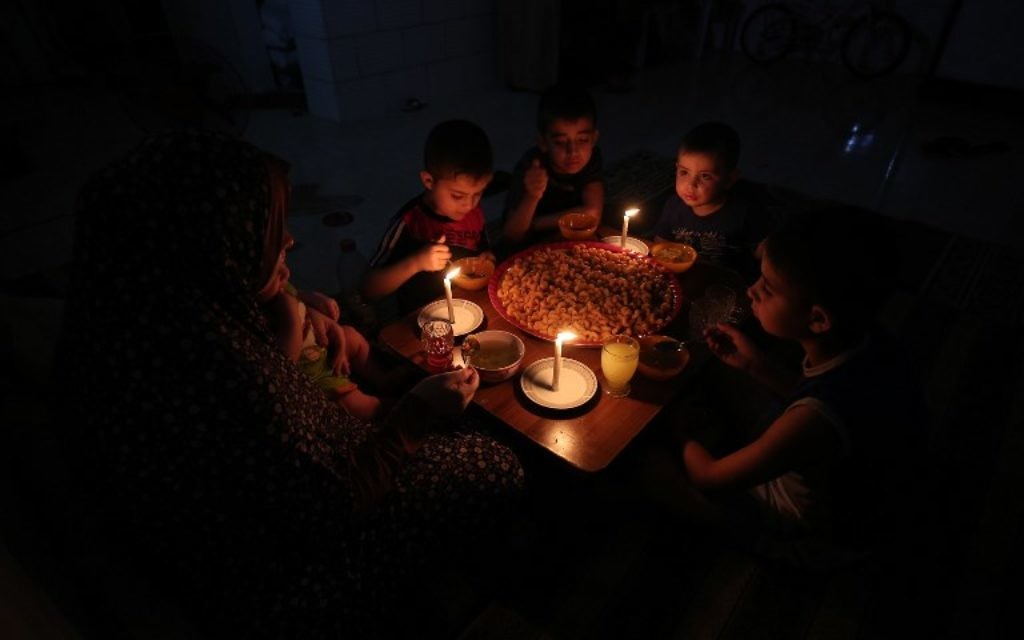 A Palestinian family eats dinner by candlelight at their makeshift home in the Rafah refugee camp, in the southern Gaza Strip, during a power outage June 11, 2017. (AFP/SAID KHATIB)