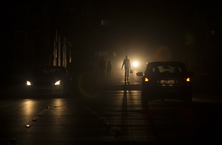Palestinians walk on a darkened street during a power outage in the Al-Shati refugee camp in Gaza City, June 11, 2017. (AFP/MAHMUD HAMS)