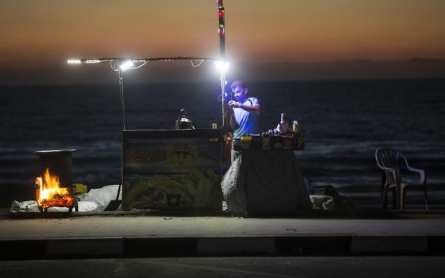 A Palestinian street vendor stands behind his stall in front of the beach in Gaza City during a power outage on June 11, 2017. (AFP/MAHMUD HAMS)