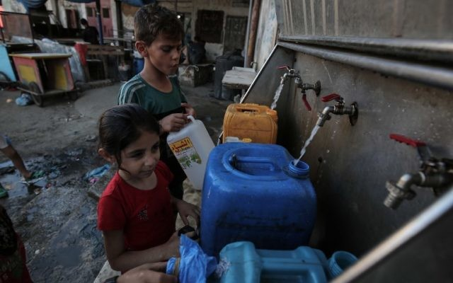 Palestinian children fill jerrycans with drinking water from public taps in the southern Gaza Strip, June 11, 2017. (AFP/SAID KHATIB)