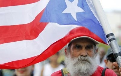 A man carries a Puerto Rican flag during a protest against the referendum for Puerto Rico political status in San Juan, on June 11, 2017. (AFP PHOTO / Ricardo ARDUENGO)