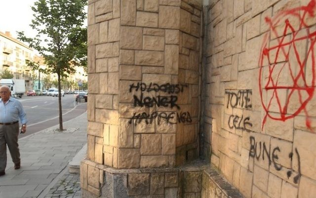 "A man walk past the wall of a Synagogue with 'Holocaust never happened' and ""All the best!' written on it in Cluj-Napoca, Romania, June 12, 2017 (AFP PHOTO / MIRCEA ROSCA)"