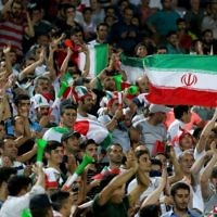 Illustrative: Supporters of the Iranian national soccer team cheer during the 2018 World Cup qualifying match between Iran and Uzbekistan at the Azadi Stadium in Tehran on June 12, 2017. (AFP Photo/Atta Kenare)