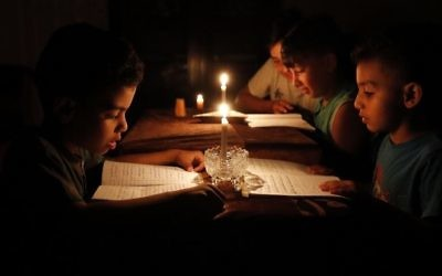 A picture taken on June 13, 2017, shows Palestinian children at home reading books by candle light due to electricity shortages in Gaza City. (AFP/ THOMAS COEX)
