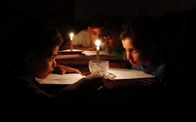 Palestinian children at home reading books by candle light due to electricity shortages in Gaza City, June 13, 2017. (AFP/Thomas Coex)