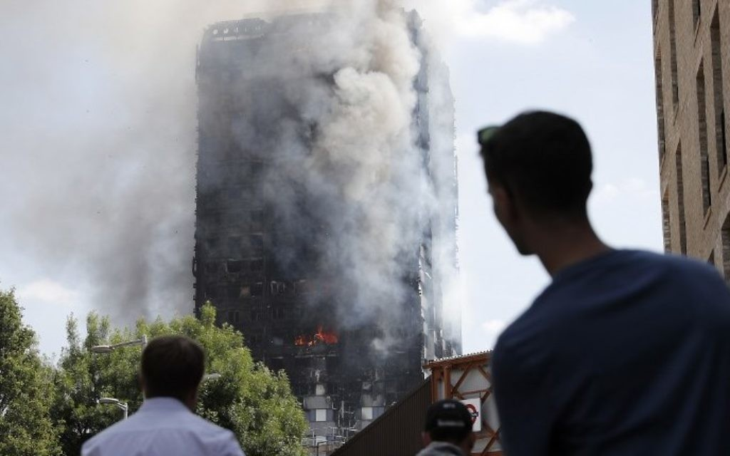 Pedestrians look up towards Grenfell Tower, a residential block of flats in west London on June 14, 2017, as firefighters continue to control a fire that engulfed the building in the early hours of the morning. (AFP PHOTO / Adrian DENNIS)