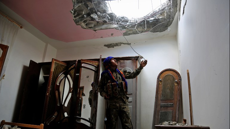 A member of the Syrian Democratic Forces (SDF), made up of an alliance of Kurdish and Arab fighters, looks at the damage in a neighbourhood on the eastern front of the Islamic State (IS) group's Syrian bastion of Raqa after seizing the area from the jihadists on June 14, 2017. (DELIL SOULEIMAN / AFP)