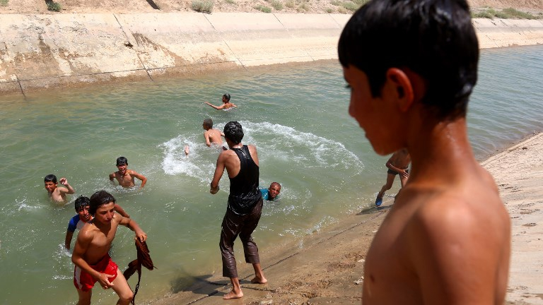 Displaced Syrian children from Raqa bath at a water canal near the al-Karamah camp, some 20 kilometers east of the Islamic State (IS) group's Syrian bastion, on June 13, 2017. (DELIL SOULEIMAN / AFP)