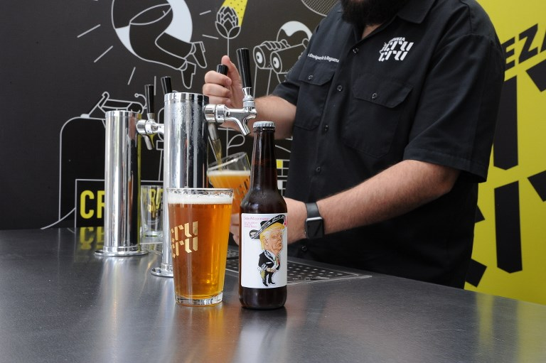 Cru Cru Brewery CEO Luis Enrique de la Reguera serves an Amigous Craft Beer which bottle shows an image of US President Donald Trump wearing a Mariachi costume and swastika belt buckle, in Mexico City, on June 15, 2017. (AFP PHOTO/Bernardo Montoya)