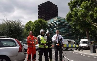 London Police Commander Stuart Cundy (R), joined by firemen and an emergency worker, makes a statement to the media against the backdrop of the remains of Grenfell Tower, a residential tower block in west London which was gutted by fire, in west London on June 16, 2017. (Daniel LEAL-OLIVAS / AFP)