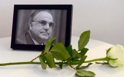 A photograph of former German Chancellor Helmut Kohl and a white rose are seen next to a book of condolences for Kohl at the conservative Christian Democratic Union's regional party congress in Berlin on June 17, 2017. (Maurizio Gambarini/DPA/AFP)