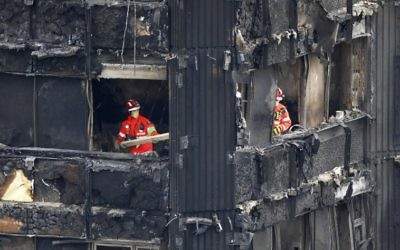 Members of the emergency services work on the middle floors of the charred remnains of the Grenfell Tower block in Kensington, west London, on June 17, 2017, follwing the June 14 fire at the residential building. ( AFP PHOTO / Tolga AKMEN)