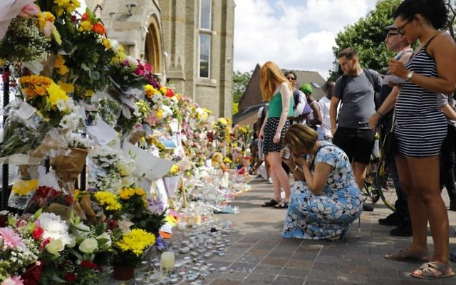People look at floral tributes outside the Notting Hill Methodist Church, left for the victims of the June 14 Grenfell Tower block fire, in Kensington, west London, on June 17, 2017. (AFP PHOTO / Tolga AKMEN)