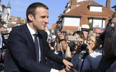 French President Emmanuel Macron shakes hands with people as he arrives to vote in Le Touquet, northern France, during the second round of the French parliamentary elections on June 18, 2017 (AFP PHOTO / POOL / CHRISTOPHE ARCHAMBAULT)