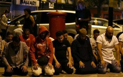 Muslims pray on a sidewalk in the Finsbury Park area of north London after a vehicle hit pedestrians, on June 19, 2017. (AFP PHOTO/Daniel LEAL-OLIVAS)