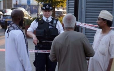 A police officer talks with residents in the Finsbury Park area of north London after a vehicle hit pedestrians, on June 19, 2017. (Daniel LEAL-OLIVAS / AFP)