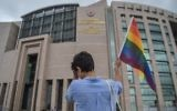 A person waves a rainbow flag in front of Istanbul courthouse on June 19, 2017 in support to eleven LBTG activists who went on trial for having marched during last year's Gay Pride, which was banned.  (AFP PHOTO / OZAN KOSE)