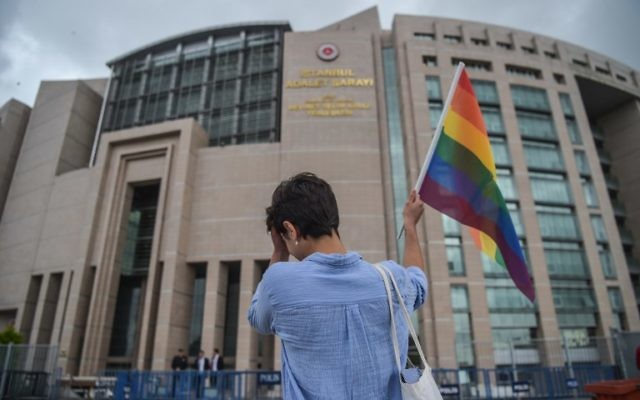 A person waves a rainbow flag in front of Istanbul courthouse on June 19, 2017, in support of eleven LGBT activists who went on trial. (AFP Photo/Ozan Kose)
