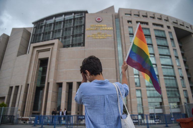 A person waves a rainbow flag in front of Istanbul courthouse on June 19, 2017 in support to eleven LBTG activists who went on trial. (AFP PHOTO / OZAN KOSE)