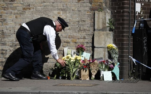 A police officer lays flowers inside a police cordon near the scene in Finsbury Park area of north London after a vehicle was driven into pedestrians, on June 19, 2017. (AFP PHOTO/Tolga AKMEN)