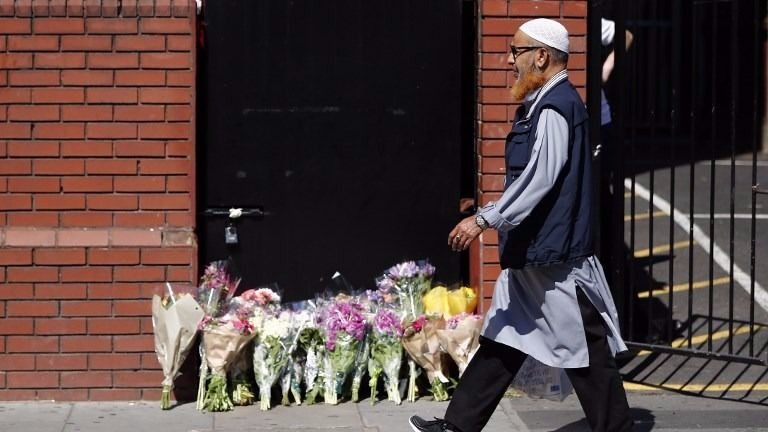 A man walks past floral tributes outside Finsbury Park Mosque in the Finsbury Park area of north London, on June 19, 2017, near to where a vehicle was driven into pedestrians. (Tolga AKMEN / AFP)
