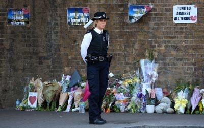 A police officer stands on duty near tributes and flowers at a police cordon in the Finsbury Park area of north London on June 19, 2017. (AFP/ Isabel INFANTES)