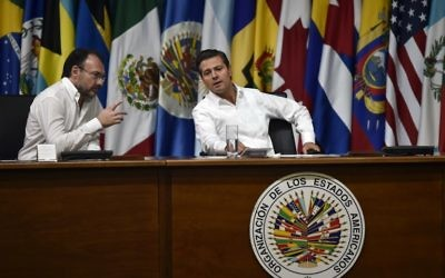 Mexican President Enrique Pena Nieto (R) and Foreign Minister Luis Videgaray gesture during the opening ceremony of the OAS 47th General Assembly in Cancun, Mexico, on June 19, 2017. (AFP/Pedro Pardo)