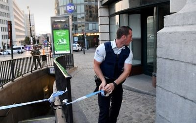 A police official is watched by a soldier as he uses tape to cordon off an area outside Gare Centrale in Brussels on June 20, 2017, after an explosion in the Belgian capital. (AFP PHOTO / Emmanuel DUNAND)