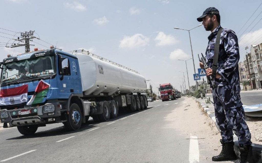 Palestinian security forces stand guard as Egyptian trucks carrying fuel drive down a street after entering the southern Gaza Strip from Egypt through the Rafah border crossing on June 21, 2017. (AFP PHOTO / SAID KHATIB)