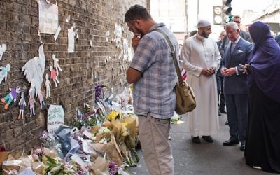 Britain's Prince Charles, Prince of Wales (3rd R) and Imam Mohammed Mahmoud (2nd L) visit floral tributes left close to the scene of the Finsbury Mosque attack in the Finsbury Park area of north London on June 21, 2017, following a car-ramming terror attack on pedestrians. (AFP/Pool/John Nguyen)