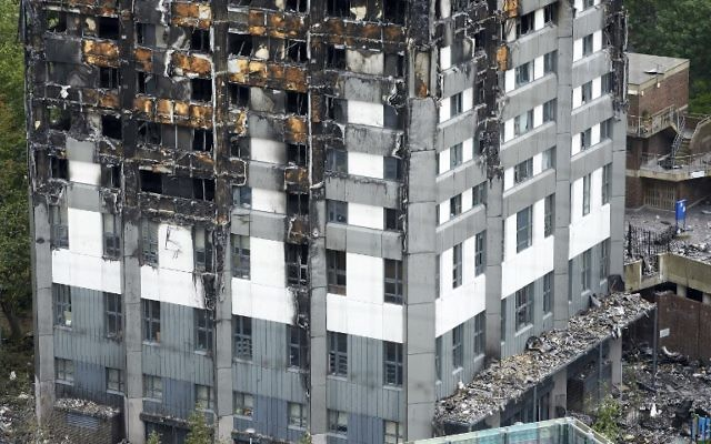The unburned lower floors with untouched cladding still in place are pictured, with the burnt out upper floors above, at remains of the Grenfell Tower block in north Kensington, west London on June 22, 2017. (AFP PHOTO / NIKLAS HALLE'N)