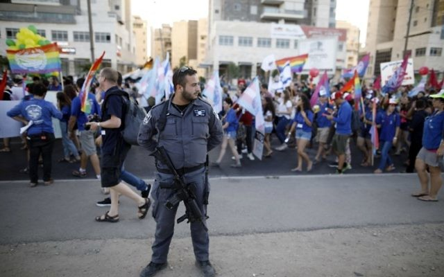 An Israeli policeman stands guard as Israelis take part in the first annual Gay Pride parade in the southern Israeli city of Beersheba, on June 22, 2017.(AFP PHOTO / MENAHEM KAHANA)