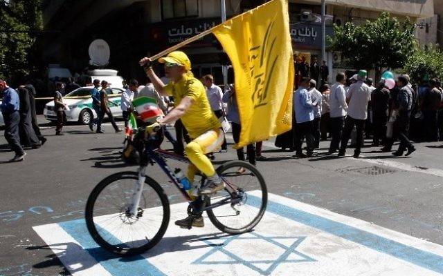 An Iranian man rides his bicycle on top of a reproduction of an Israeli flag painted on the street during a rally marking al-Quds (Jerusalem) Day in Tehran on June 23, 2017. (AFP Photo/Stringer)