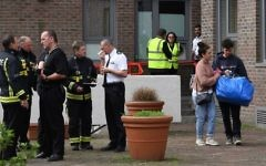 Residents (R) with belongings leave Burnham Tower residential block on the Chalcots Estate in north London on June 24, 2017 as residents evacuate because of fire safety concerns. ( AFP PHOTO / Justin TALLIS)