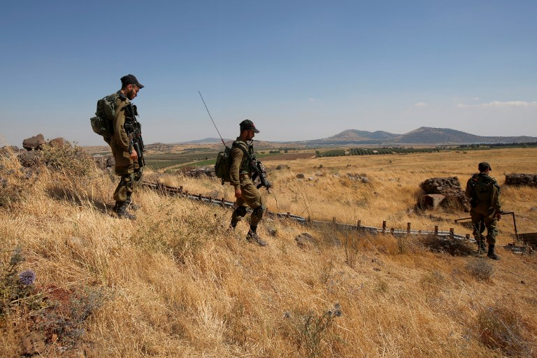 Israeli soldiers patrol near the border with Syria after projectiles fired from the war-torn country hit the Israeli Golan Heights on June 24, 2017. (AFP PHOTO / JALAA MAREY)