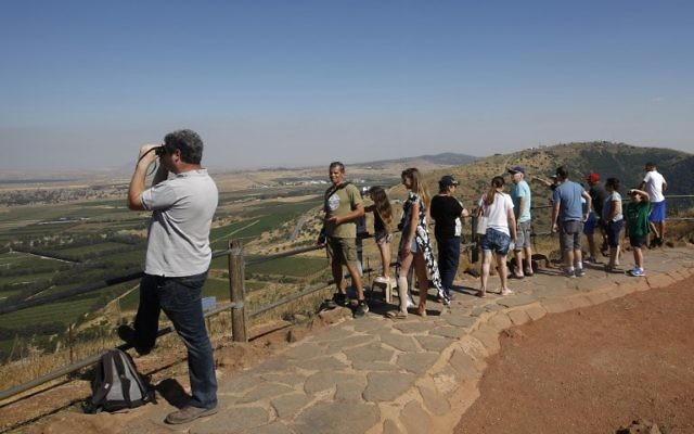 Israeli tourists look at the Syrian side of the border from Mount Bental, in the Israeli Golan Heights, after projectiles fired from the war-torn country hit the Golan on June 24, 2017. (AFP PHOTO / JALAA MAREY)