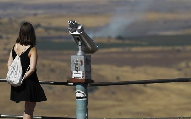 An Israeli tourist looks at the Syrian side of the border from Mount Bental, in the Golan Heights, on June 25, 2017. (AFP Photo/Jalaa Marey)