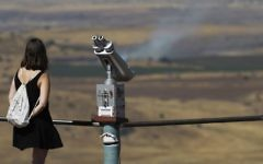 An Israeli tourist looks at the Syrian side of the border from Mount Bental, in the Golan Heights, on June 25, 2017.(AFP PHOTO / JALAA MAREY)