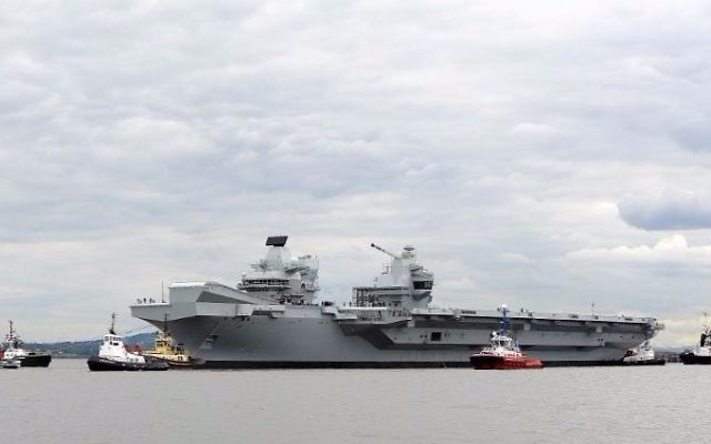 Tug boats maneuver the 65,000-ton British aircraft carrier HMS Queen Elizabeth on the Firth of Forth in east Scotland, on June 26, 2016, after escorting it out of its berth in Rosyth Naval dockyard to begin sea trials. (Andy Buchanan/AFP)
