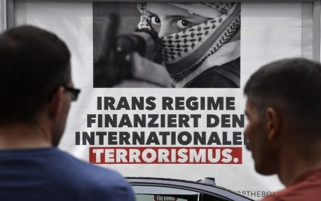 """Onlookers stand in front of a poster reading """"Iran's regime finances international terrorism"""" during a demonstration in front of the Foreign Ministry as German Vice Chancellor and Foreign Minister Sigmar Gabriel and his Iranian counterpart Mohammad Javad Zarif meet in Berlin on June 27, 2017. (John Macdougall/AFP)"""