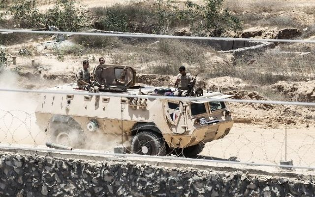 A picture taken on June 28, 2017 from the Gaza strip border-town of Rafah shows Egyptian border guards patrolling on the other side of the border while riding in an armored personnel carrier. (AFP PHOTO / SAID KHATIB)