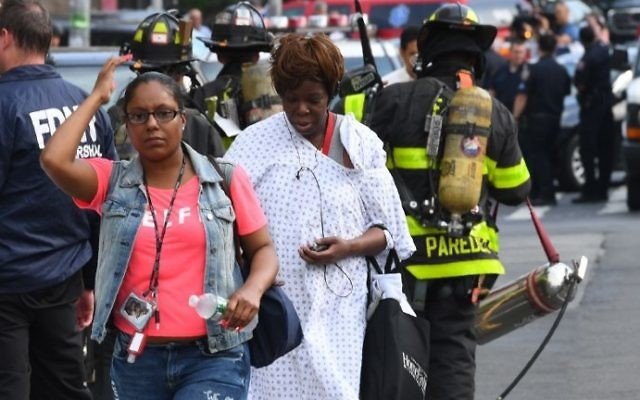 A patient walks past fire fighters at the Bronx-Lebanon Hospital as police respond to an active shooter north of Manhattan in New York on June 30, 2017.( AFP PHOTO / TIMOTHY A. CLARY)