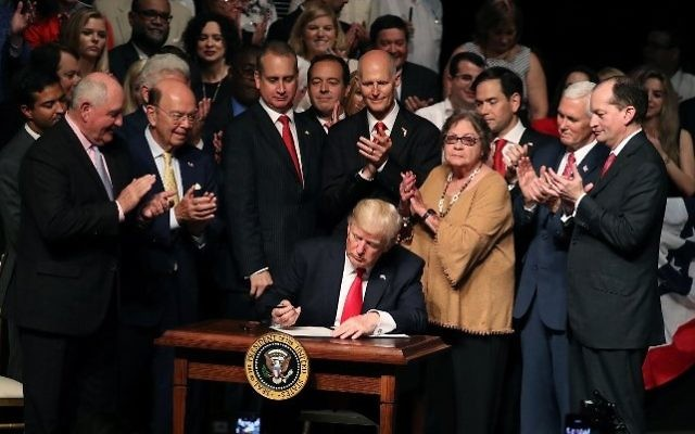 US President Donald Trump signs policy changes he is making toward Cuba at the Manuel Artime Theater in the Little Havana neighborhood on June 16, 2017 in Miami, Florida. (Joe Raedle/Getty Images/AFP)