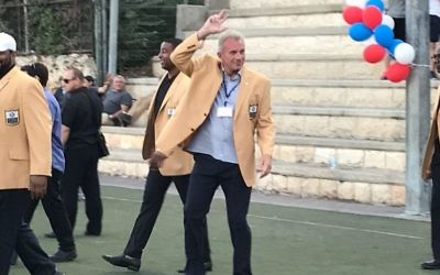 Joe Montana (middle) waves to fans at Kraft Family Stadium in Jerusalem on June 18, 2017. (Jacob Magid/Times of Israel)