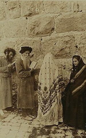Two Jewish men and two women stand in front of the Western Wall, Jerusalem, circa 1908. (Underwood & Underwood/Library of Congress)