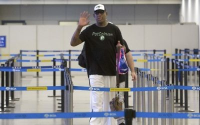 Former NBA basketball player Dennis Rodman gestures to photographers as he prepares to go through immigration at Beijing Capital International Airport in Beijing, Tuesday, June 13, 2017. (AP Photo/Mark Schiefelbein)