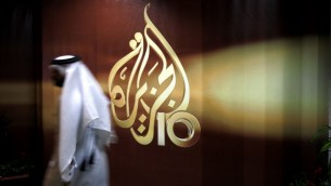 A Qatari employee of al-Jazeera TV walks past the logo of Al Jazeera in Doha, Qatar, November 1, 2006 (AP Photo/Kamran Jebreili, File)