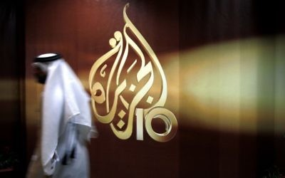 A Qatari employee of al-Jazeera TV walks past the station's logo, in Doha, Qatar, November 1, 2006. (AP Photo/Kamran Jebreili, File)