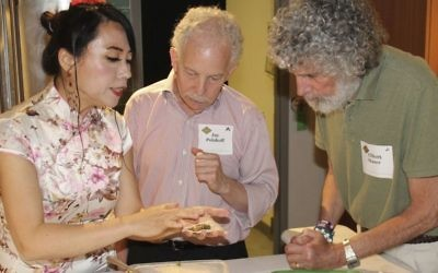 In this photo provided by Alex Styer, Alice Ye, left, demonstrates her technique for folding dumplings to Jay Polakoff, center, and Elliott Maser, right, during a June 5, 2017, dinner at Reading Terminal Market in Philadelphia. (Alex Styer/Bellevue Communications Group via AP)