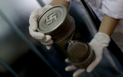 Illustrative: A member of the federal police holds an hourglass with Nazi markings at the Interpol headquarters in Buenos Aires, Argentina, June 16, 2017. (AP/Natacha Pisarenko)